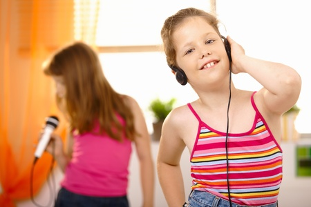 Young happy girl listening to music via headphones, smiling, friend singing in background. photo