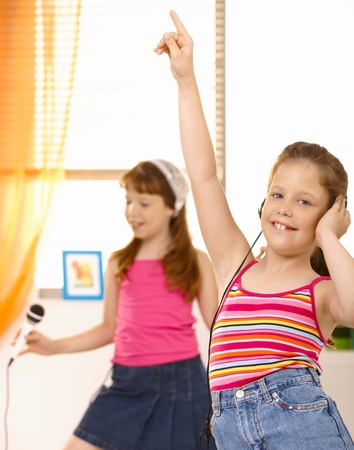 Schoolgirls having fun with headset and microphone, dancing at home. photo