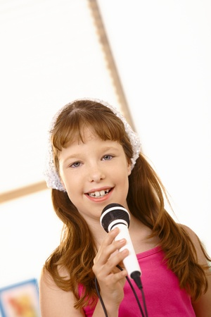 Portrait if young girl singing with microphone in hand, smiling at camera. Stock Photo - 8784190