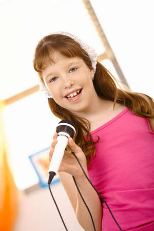 Portrait of schoolgirl singer, looking at camera, smiling, holding microphone. photo