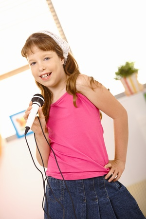 Cute schoolgirl performing song with microphone, looking at camera, posing and smiling. photo