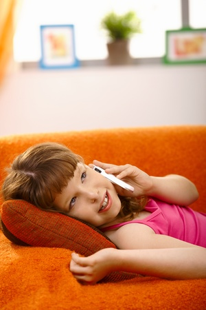 Schoolgirl lying on couch talking on mobile phone, smiling, photo