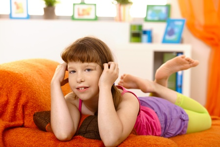 Little girl lying on sofa, looking at camera, smiling. photo