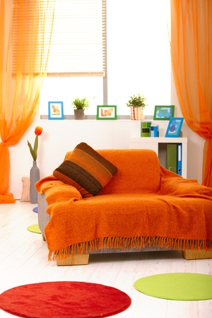 cosy: Bright colorful living room with armchair covered in orange. Stock Photo