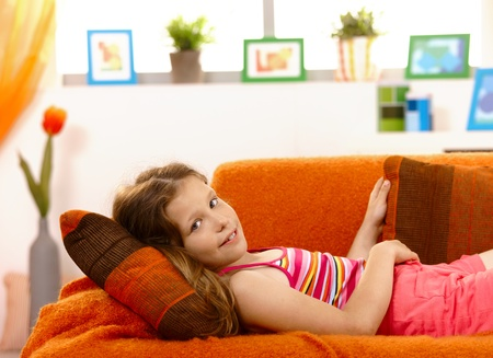 Portrait of young girl lying on couch at home, looking at camera, smiling. photo