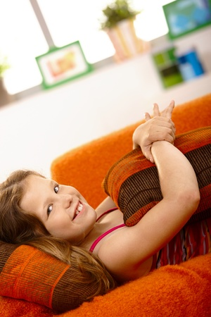 Happy schoolgirl lying on couch in living room, holding cushion, laughing at camera. photo