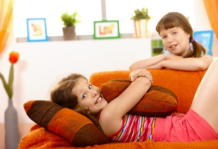 Cute small girl relaxing on sofa, smiling, hugging pillow, friend in background. Stock Photo - 8784503