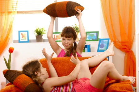 pillow fight: Schoolgirls playing pillow fight on sofa in living room.