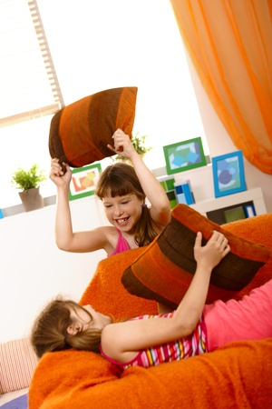 Small girls having fun in pillow fight on couch, laughing. photo