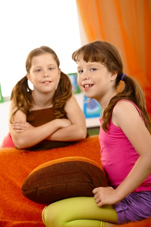 Portrait of schoolgirl sitting on couch in living room, with friend in background, smiling at camera. Stock Photo - 8784753