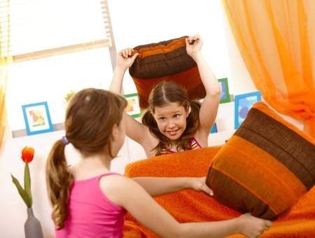 Pillow fight: Happy schoolgirls in pillow fight in living room.