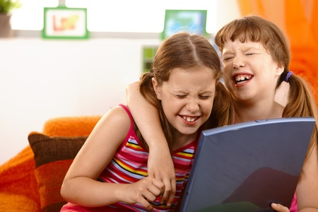 Cute girl friends laughing at laptop computer screen, hugging. photo