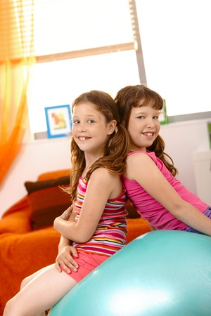 Young girls sitting on exercise ball together, having fun. photo