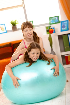 Small girls playing with gym ball in living room, smiling at camera. photo