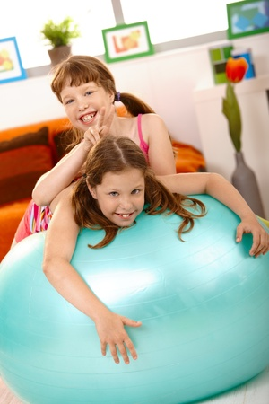Schoolgirl teasing friend on gym ball, showing dogs-ear, laughing. photo