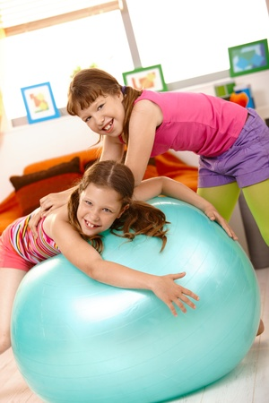 Little girls playing with exercise ball at home, laughing. Stock Photo - 8784185