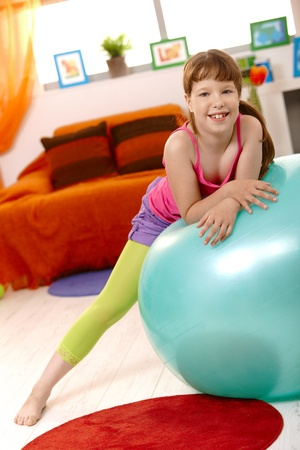 Schoolgirl with exercise ball in living room, laughing at camera. photo