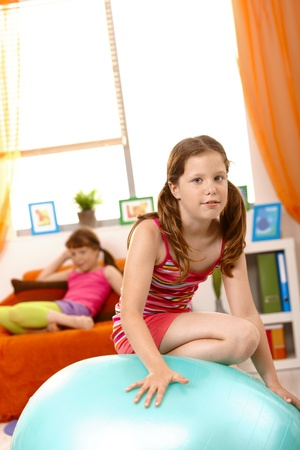 Young girl climbing on gym ball in living room, friend in background on sofa. Stock Photo - 8784019