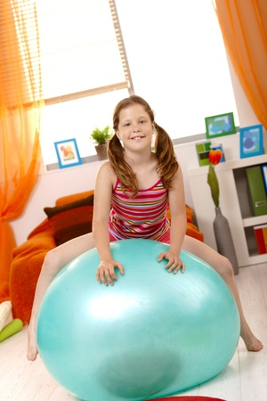 Young girl sitting on gym ball in living room, looking at camera, smiling. photo