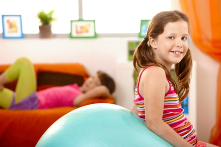 Happy young girl sitting on gym ball at home. photo