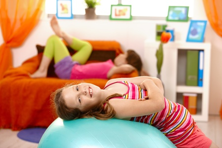 Laughing schoolgirl lying on gym ball, looking at camera, friend lying on sofa in background. Stock Photo - 8784192