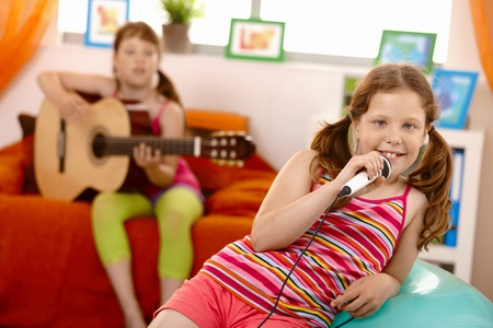 Young girl smiling at camera with microphone in hand at home, friend playing guitar. photo