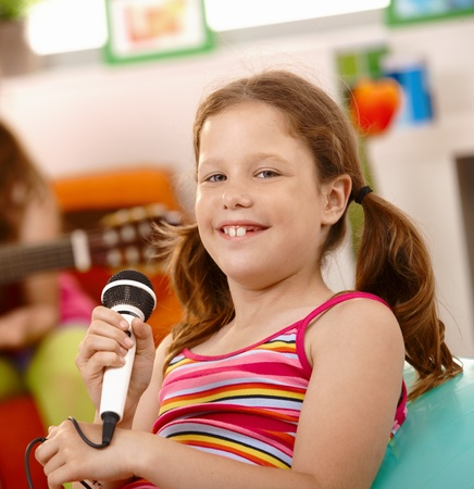Closeup portrait of happy schoolgirl with microphone, smiling at camera. Stock Photo - 8783840