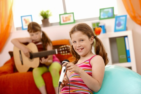 Young girls having fun with music at home, playing guitar, singing with microphone. photo