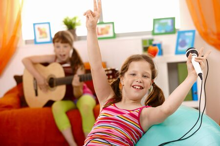 Small laughing girl with microphone, raising arms happily, friend playing guitar. photo
