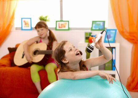 Young girl singing into microphone, having fun with guitar player friend at home. photo