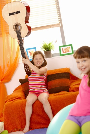 Small smiling girl raising guitar high by neck on sofa at home. photo