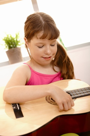 Closeup portrait of small girl playing guitar, smiling. photo