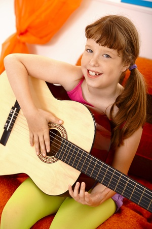Portrait of cute schoolgirl with guitar, laughing at camera. photo