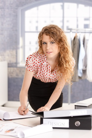 Young attractive fashion designer working in office at desk. photo