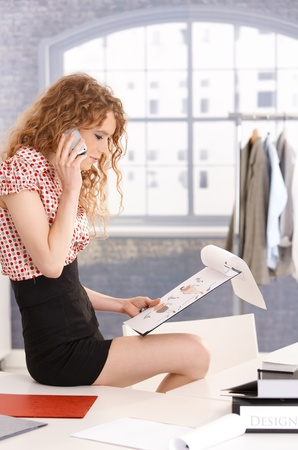 Pretty fashion designer working in office using mobile phone, sittin on table. photo