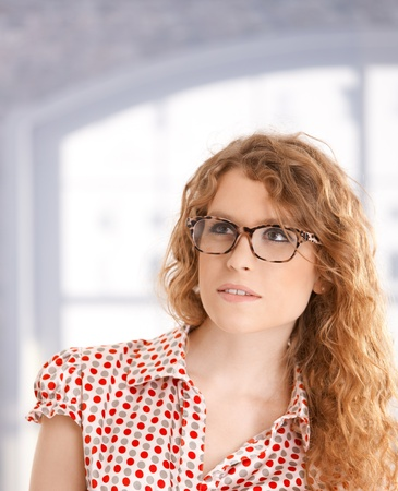 Portrait of pretty young girl front of window wearing glasses. photo