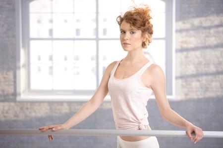 Pretty ballerina girl standing by bar in dance studio front of window. photo