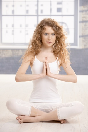 Attractive young female practicing yoga, meditating in prayer pose, eyes open, sitting on floor front of window. Stock Photo - 8784137