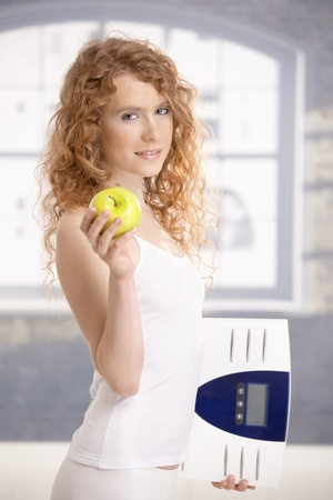 Pretty female holding apple and scale in hands, dieting. photo