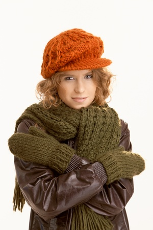 Attractive young woman dressed up warm, arms crossed, freezing. photo