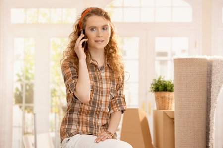 Pretty girl moved to new home, sitting on boxes, smiling, using mobile phone. photo