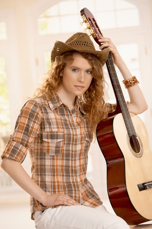Attractive girl leaning on guitar, sitting, dressed in western style. photo