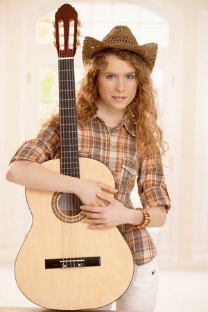Pretty guitarplayer girl embracing her guitar, dressed in country style. photo