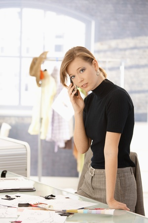 Young attractive female fashion designer talking on mobile phone in office, looking at camera. photo