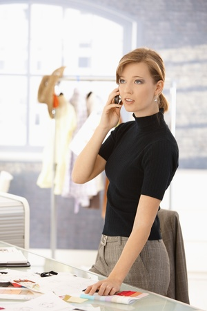 Young attractive female fashion designer talking on mobile phone, selecting color samples on office desk. photo