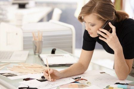designer: Young attractive female fashion designer working at office desk, drawing while talking on mobile.