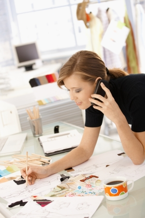 designer clothes: Young attractive female fashion designer working at office desk, drawing while talking on mobile.