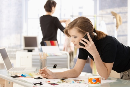 designing: Young attractive female fashion designer leaning on office desk, talking on mobile phone.