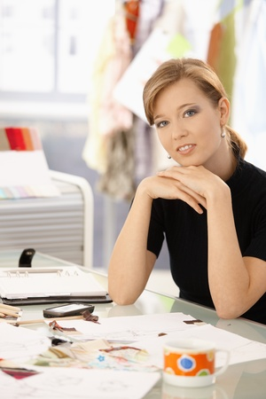 Young attractive female fashion designer leaning on office desk, thinking. photo