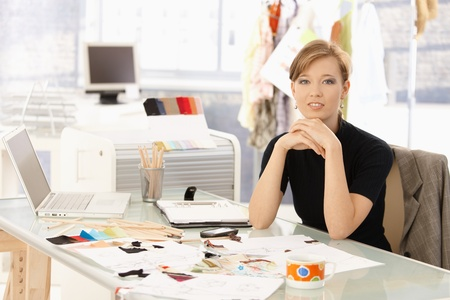 office wear: Portrait of attractive female fashion designer sitting at office desk, smiling. Stock Photo